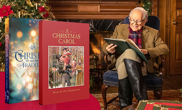 Pat Robertson in festive gard reading A Christmas Carol while sitting by the fireplace.