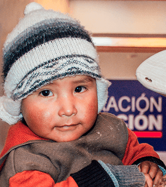 Peruvian Boy wearing a stocking hat with rosy red cheeks.