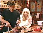Randy Travis cuts the roast beef at their home in Santa Fe, New Mexico, while wife Liv looks on