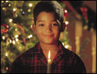 christmas Devotion < young boy in plaid pajamas holding a single lit candle with christmas tree in background