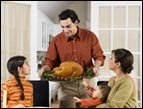 daily Devotion picture of man carrying a platter with a turkey to set on table in front of wife, daughter and baby