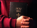 arms and hands of person wearing a dark red shirt holding a black Holy Bible with a cross on it