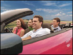 family riding in a red convertible on a road trip