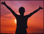 person silhouette with hands in air and sunrise in background