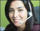 woman with brown hair and brown eyes with a telephone headset on her head