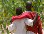 two African boys from the back walking toward a field with arms around each other