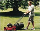 man mowing grass wearing shorts and tennis shoes