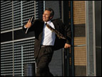 businessman hurrying out a door wearing a suit and tie and carrying a laptop