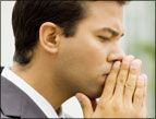 daily Devotion man wearing suit and dress shirt praying with sincerity
