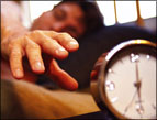 daily Devotion finding god's timing - sleeping person hand reaching for alarm clock