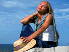 daily Devotion woman wearing jeans by the seashore sunning herself