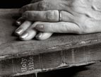 elderly woman's hands resting on worn Bible