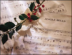 daily Devotion picture of christmas sheet music and a sprig of holly with berries