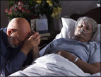 daily Devotion picture of man knealing in prayer beside hospital bed with elderly woman in it.