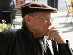 daily Devotion picture of elderly man sitting alone in a public place outside wearing a brown cap, glasses and a leather jacket