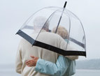 daily Devotion older couple in rain under umbrella