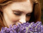 a red head woman smelling lavender flowers