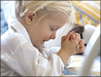 daily Devotion picture of little blonde child praying with eyes closed and hands clasped