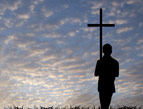 young man silhouette with cross of Christ