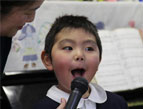 Kindergarteners and staff perform special songs in gratitude for the gift of a new bus.