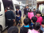 Children unload from their new bus that can now take them on field trips a safe distance away.