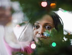 woman placing christmas ornament on christmas tree