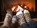 socks on feet propped up near fireplace