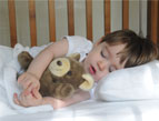 toddler sleeping with stuffed bear