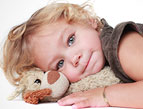 toddler cuddling with stuffed animal toy