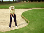 woman playing golf sand trap