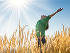woman happy with the sunrise in a wheat field