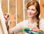 redhead woman painting with palette on canvas