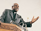 Devotion - black man preacher priest bishop clergy preaching at pulpit with microphone