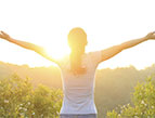 woman happy raising arms at sunrise