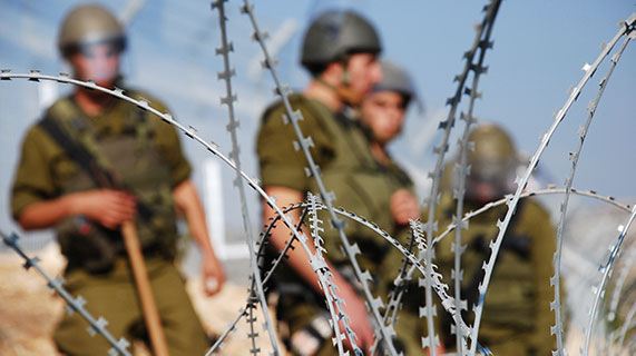 Armed soldiers standing guard in the distance, with the camera focused on barbed-wire in the foreground.